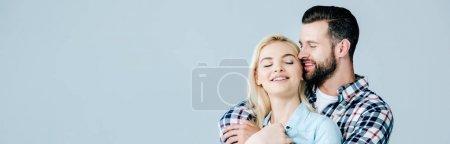 Photo pour Plan panoramique d'un bel homme embrassant une belle jeune femme souriante isolée sur du gris - image libre de droit