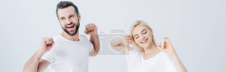 panoramic shot of happy man and young woman stretching with clenched fists isolated on grey
