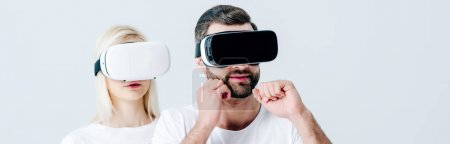 Photo for Panoramic shot of man with clenched fists and girl in Virtual reality headsets isolated on grey - Royalty Free Image