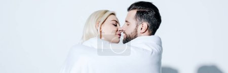 Photo for Panoramic shot of girlfriend and boyfriend covered in blanket ready for kissing on white - Royalty Free Image