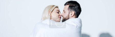 Photo pour Tir panoramique de petite amie et petit ami couvert d'une couverture prête à s'embrasser sur le blanc - image libre de droit