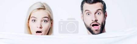panoramic shot of shocked girlfriend and handsome boyfriend holding blanket isolated on white