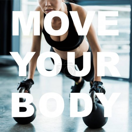 Photo for Cropped view of girl in sportswear exercising with dumbbells near move your body letters - Royalty Free Image