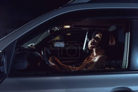Photo for Thief attacking beautiful frightened woman in automobile at night - Royalty Free Image