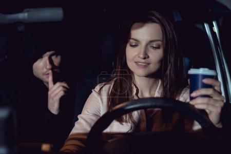 Photo pour Voleur faisant le geste silencieux près de la belle femme de sourire dans la voiture - image libre de droit