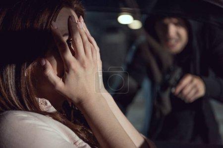Photo for Thief pointing gun at woman sitting in car at night - Royalty Free Image