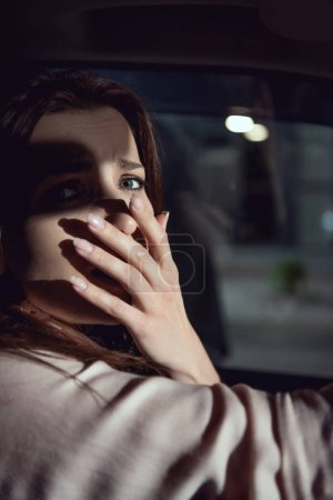 Photo for Scared woman looking at camera and covering mouth in car - Royalty Free Image