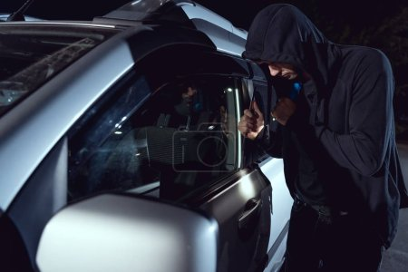 Photo for Thief intruding car with flashlight and crowbar at night - Royalty Free Image