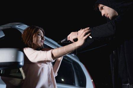 Photo for Thief pointing gun at terrified woman near car at night - Royalty Free Image