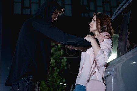 Photo pour Voleur attaquant femme terrifiée près de la voiture la nuit - image libre de droit