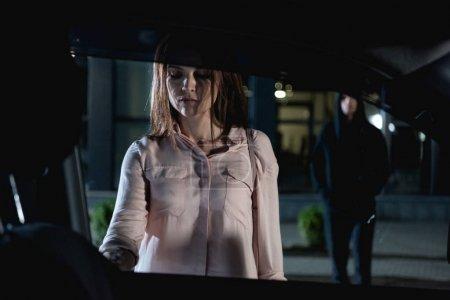 Photo pour Voleur suivant belle femme ouvrant voiture la nuit - image libre de droit