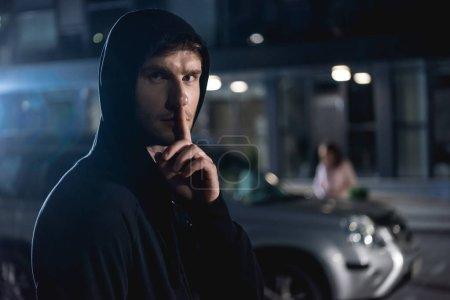Photo pour Mise au point sélective du voleur regardant la caméra et faisant geste de silence - image libre de droit