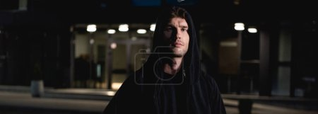Photo for Panoramic shot of thief in black hoodie looking at camera in parking lot at night - Royalty Free Image