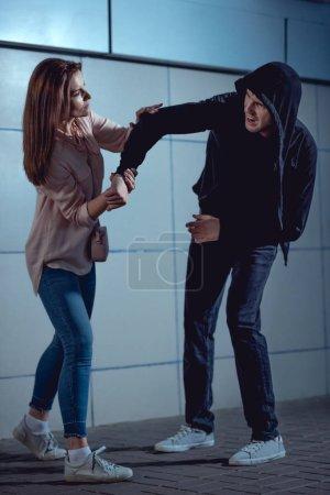 Photo pour Attrayant femme se battant avec voleur dans le passage inférieur - image libre de droit