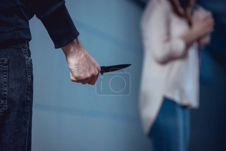 selective focus of thief with knife standing near woman