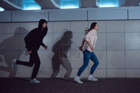 Photo pour Femme fuyant voleur en sweat à capuche dans le passage inférieur - image libre de droit