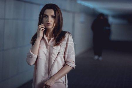 Photo pour Focus sélectif de la femme parlant sur smartphone près voleur dans le passage inférieur - image libre de droit