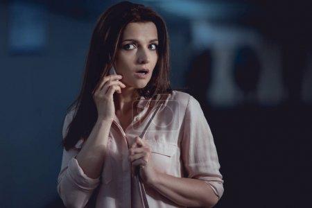 Photo pour Peur belle femme parler sur smartphone dans le passage souterrain - image libre de droit