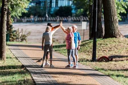 Photo for Multicultural group of retired men and women in sportswear giving high five in park - Royalty Free Image