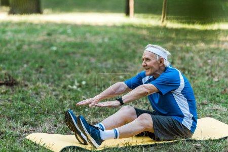 Photo pour Heureux retraité exercice sur tapis de fitness dans le parc - image libre de droit