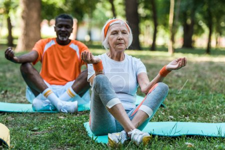 Photo for Selective focus of retired senior woman and african american man with closed eyes sitting with crossed legs in park - Royalty Free Image