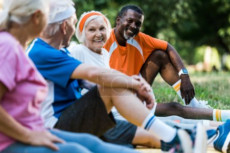 Photo for Selective focus of happy multicultural men and women in sportswear sitting on fitness mats - Royalty Free Image