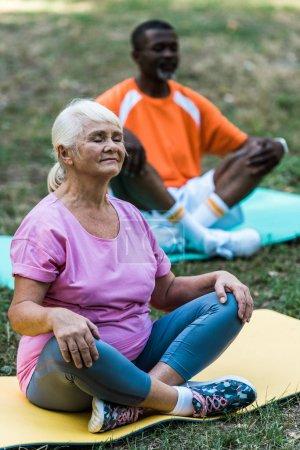 Photo pour Foyer sélectif de la femme à la retraite avec les yeux fermés s'asseyant avec les jambes croisées près de l'homme africain américain aîné dans le stationnement - image libre de droit