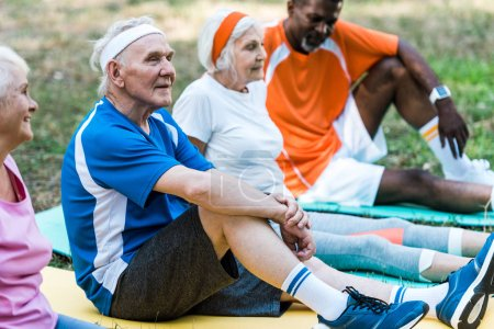 Photo for Selective focus of multicultural senior men and women in sportswear sitting on fitness mats - Royalty Free Image