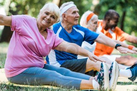 Photo pour Orientation sélective des hommes et des femmes retraités multiculturels dans les vêtements de sport s'asseyant sur des tapis de forme physique - image libre de droit