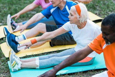 Photo for Cropped view of multicultural retired men and women in sportswear sitting on fitness mats - Royalty Free Image