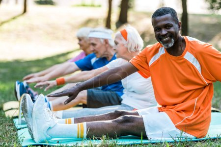 Photo for Selective focus of happy african american man near retired pensioners in sportswear exercising on fitness mats - Royalty Free Image