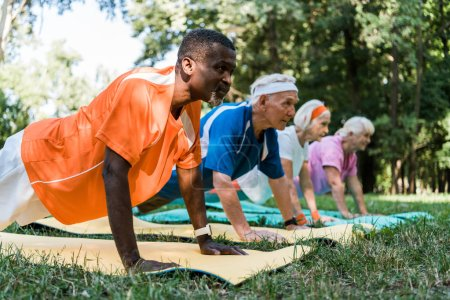 Photo for Selective focus of african american man doing plank exercise with retired pensioners on fitness mats - Royalty Free Image