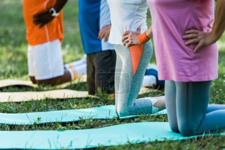 Photo for Cropped view of multicultural pensioners with hand on hips exercising on fitness mats - Royalty Free Image