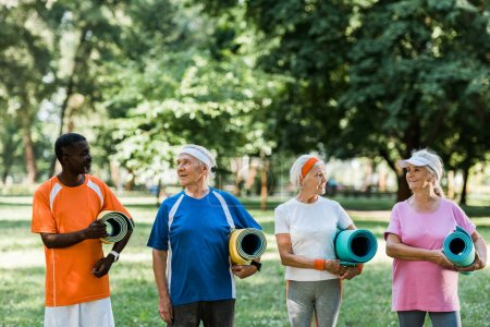 Photo for Happy senior and multicultural pensioners holding fitness mats while standing in park - Royalty Free Image