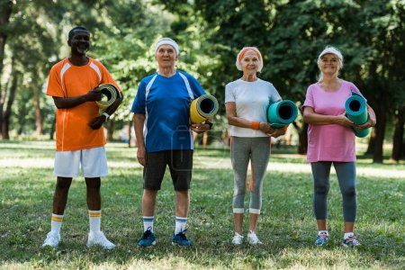 Photo for Happy retired and multicultural pensioners holding fitness mats while standing on green grass in park - Royalty Free Image