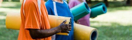Photo pour Plan panoramique de retraités âgés et multiculturels tenant des tapis de fitness - image libre de droit