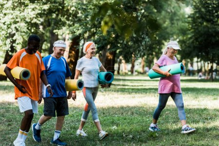 Photo for Selective focus of happy multicultural and senior pensioners walking with fitness mats in park - Royalty Free Image