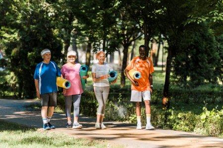 Photo pour Joyeux retraités et retraités multiculturels tenant des tapis de fitness et se promenant dans le parc - image libre de droit