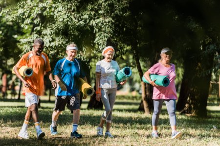 Photo for Cheerful senior and multicultural pensioners holding fitness mats and walking in park - Royalty Free Image