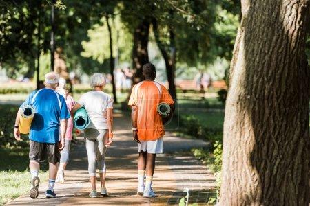 Photo pour Vue arrière des retraités aînés et multiculturels retenant des tapis de forme physique et marchant dans le stationnement - image libre de droit