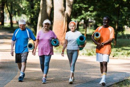 Photo pour Heureux retraités âgés et multiculturels tenant des tapis de fitness et marchant dans la passerelle dans le parc - image libre de droit