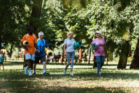 Foto de Enfoque selectivo de jubilados jubilados mayores y multiculturales pensionistas sosteniendo esteras de fitness y caminando sobre hierba - Imagen libre de derechos