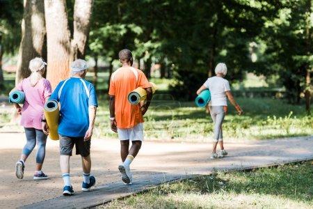 Photo pour Vue arrière des retraités aînés et multiculturels heureux retenant des tapis de forme physique et marchant sur l'herbe - image libre de droit