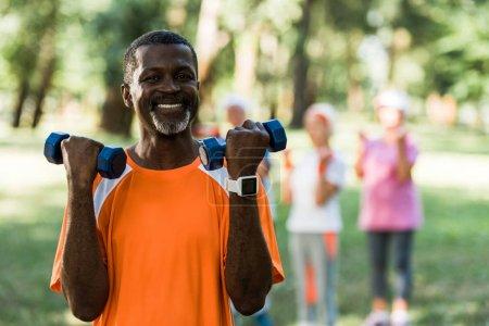 Foto de Enfoque selectivo de hombre afroamericano feliz de pie con mancuernas cerca de los pensionistas - Imagen libre de derechos