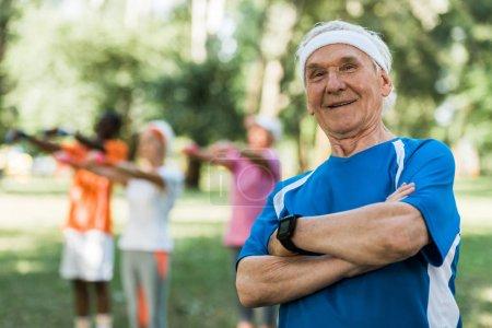 Photo pour Foyer sélectif de l'homme âgé heureux debout avec les bras croisés dans le parc - image libre de droit