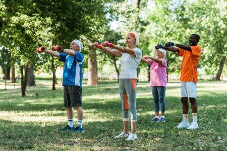 Photo pour Heureux retraités multiculturels en vêtements de sport exercice avec haltères dans le parc - image libre de droit