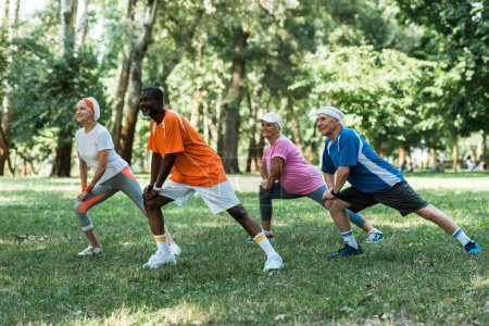 Photo for Cheerful milticultural retired men and women stretching on grass in park - Royalty Free Image