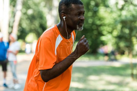 Photo for Selective focus of retired african american man running and listening music in earphones - Royalty Free Image