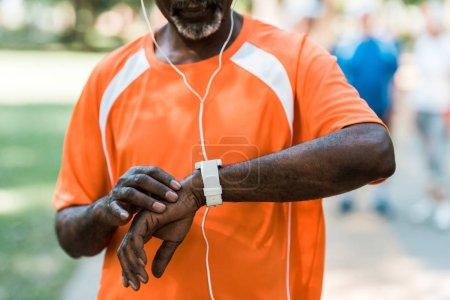 Photo pour Vue recadrée de l'homme américain africain aîné dans des écouteurs touchant la montre intelligente - image libre de droit