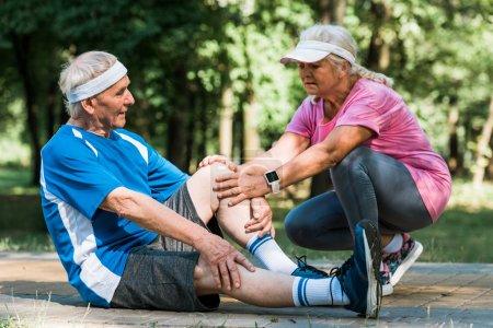Photo pour Femme bouleversée à la retraite touchant le genou de l'homme de senopr tout en s'asseyant sur la passerelle dans le stationnement - image libre de droit